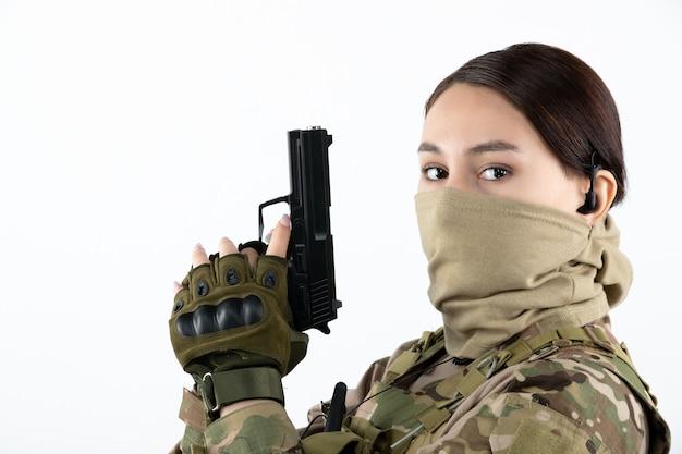 Ritratto di donna soldato con pistola in mimetica parete bianca
