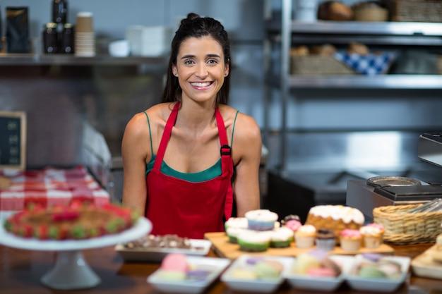 Ritratto di personale femminile in piedi al bancone in bake shop