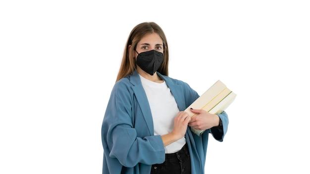 Ritratto di una studentessa o studentessa universitaria con una maschera nera e diversi libri sul braccio.