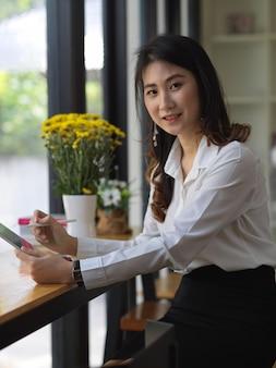 Ritratto di studentessa che esamina la macchina fotografica mentre tablet sulla barra di legno nella caffetteria