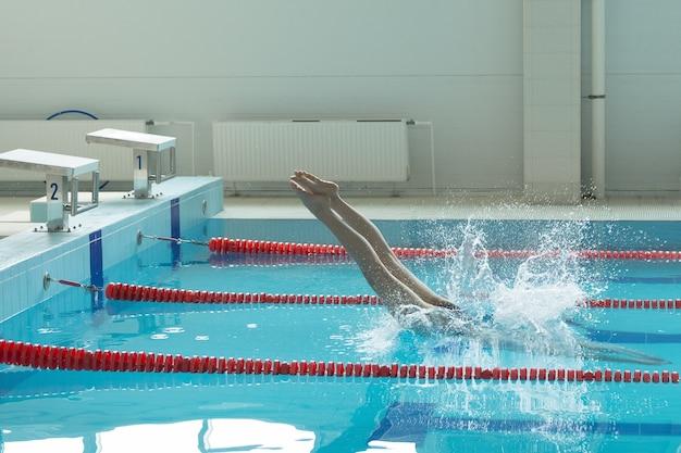 Ritratto di una nuotatrice, che salta e si tuffa nella piscina sportiva al coperto. donna sportiva.