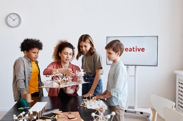 Ritratto di insegnante femminile che aiuta i bambini a realizzare modelli in legno durante le lezioni di arte e artigianato a scuola