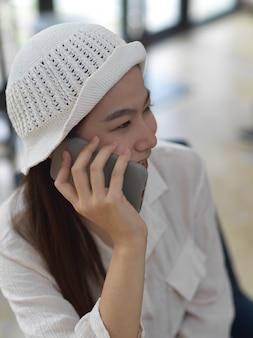 Ritratto di adolescente di sesso femminile sorridente e parlando al telefono mentre è seduto nella caffetteria