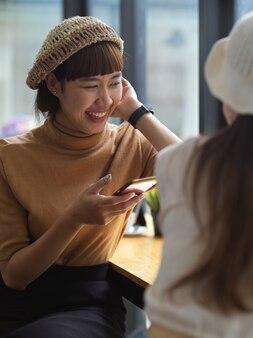 Ritratto di adolescente di sesso femminile utilizza lo smartphone e parla con un amico mentre è seduto nella caffetteria