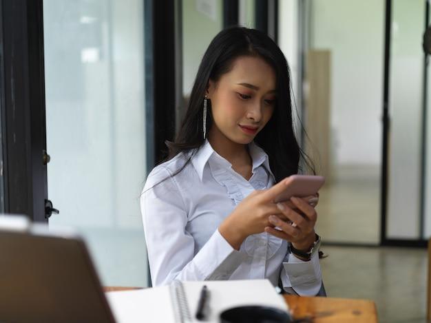 Ritratto di donna scrivere messaggi su smartphone mentre è seduto al tavolo da lavoro nella stanza dell'ufficio