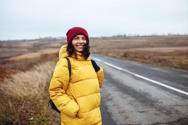 Ritratto di un turista femminile con uno zaino che indossa giacca gialla e cappello rosso si trova sulla strada.