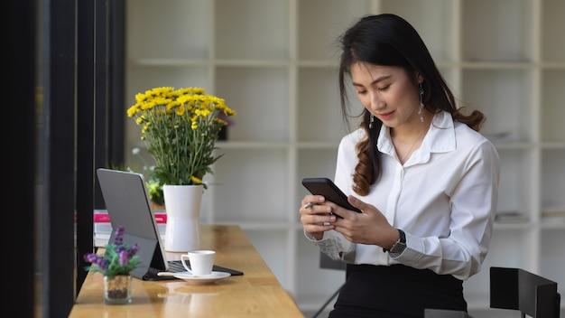 Ritratto di donna utilizza lo smartphone mentre è seduto nella caffetteria con tavoletta digitale e forniture