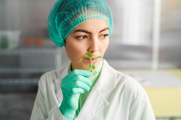 Ritratto di operaio di sesso femminile che tiene piccola pianta verde mentre si lavora in laboratorio bio, copia dello spazio