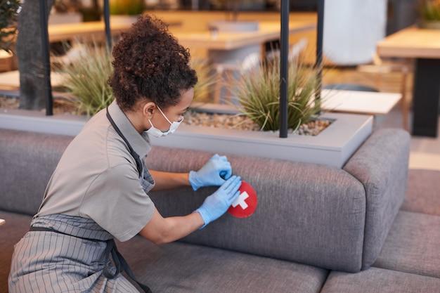 Ritratto di lavoratrice che mette adesivo di distanza sociale sul sedile del bar, concetto di sicurezza covid, spazio copia