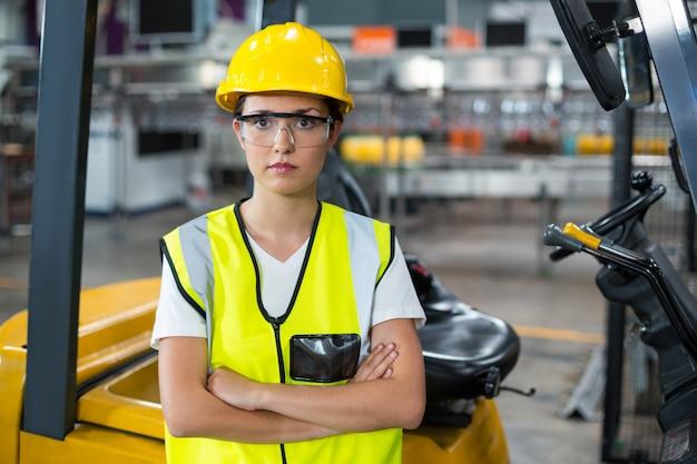 Ritratto della lavoratrice che sta con le armi attraversate