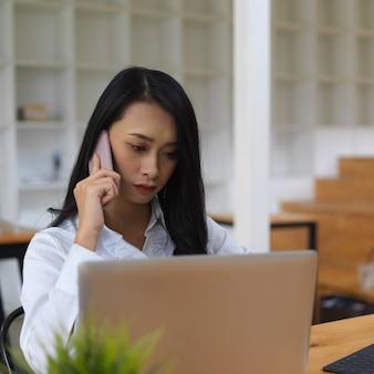 Ritratto di lavoratore di sesso femminile che parla al telefono mentre woking con il portatile in ufficio