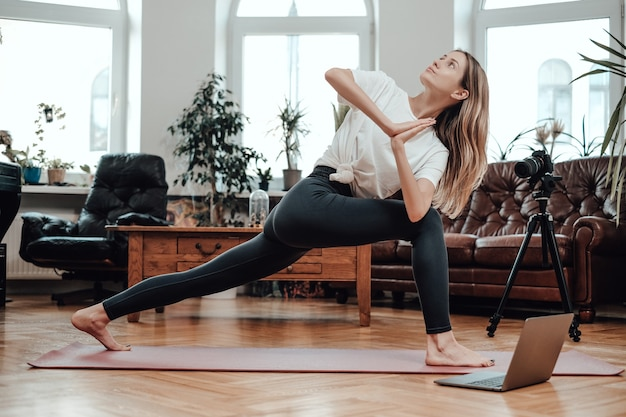 Ritratto di allenatore di yoga femminile che mostra alcune posizioni e trasmette le sue guide con laptop e fotocamera in camera.
