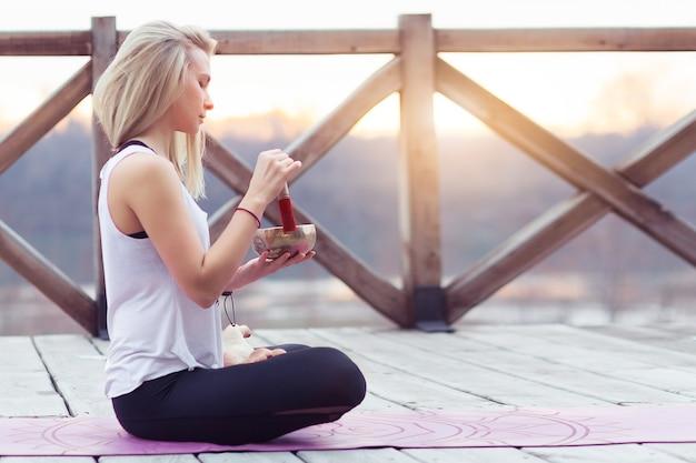 Ritratto di insegnante di yoga femminile che suona la campana tibetana o canta la campana su un ponte di legno