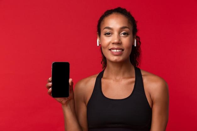 Ritratto di donna afroamericana femminile in abiti sportivi neri utilizzando smartphone e auricolari wireless, isolati sopra la parete rossa