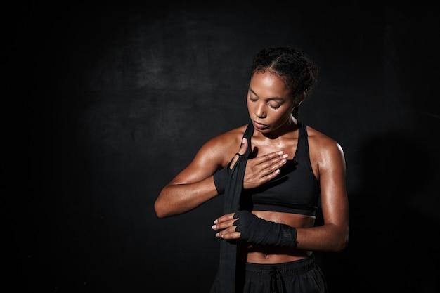 Ritratto di donna afroamericana femminile in abbigliamento sportivo che indossa involucri a mano da boxe isolati su nero