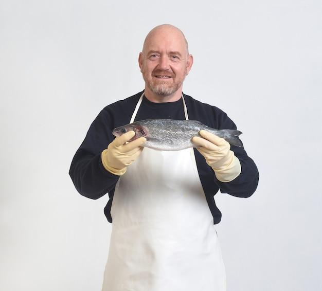 Ritratto di un pescivendolo che tiene un branzino su fondo bianco