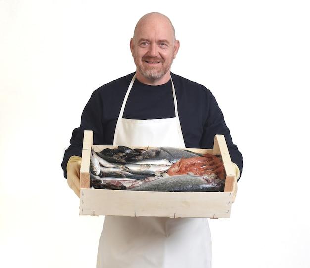 Ritratto di un pescivendolo con una scatola con frutti di mare su fondo bianco