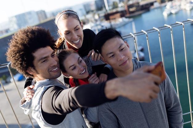 Ritratto di squadra in forma e sportiva utilizzando il telefono cellulare in città.