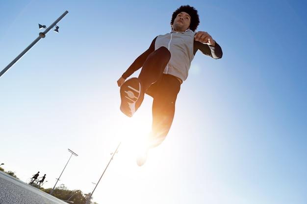 Ritratto di giovane sportivo e in forma che corre in città.