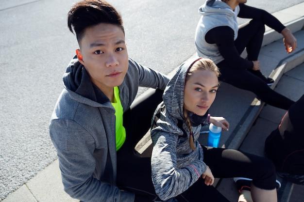 Ritratto di giovane squadra sportiva e in forma che si rilassa dopo l'allenamento in città.