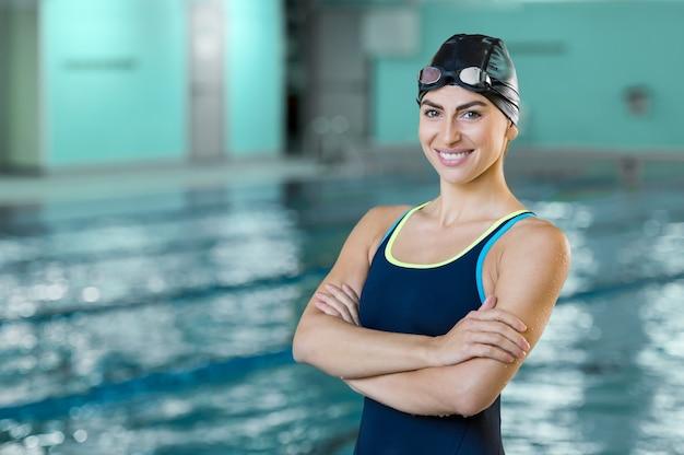 Ritratto di una donna adatta del nuotatore in piscina