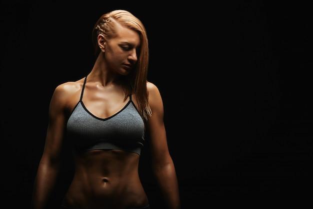 Ritratto di una giovane donna adatta che posa indossando un reggiseno sportivo contro la parete nera. atleta determinato.