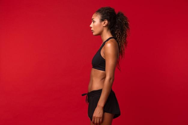 Ritratto di fitness ragazza afroamericana in abiti sportivi neri in piedi, isolato sopra la parete rossa