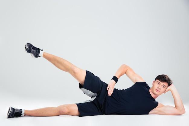 Ritratto di un uomo di forma fisica che fa esercizi di yoga isolato