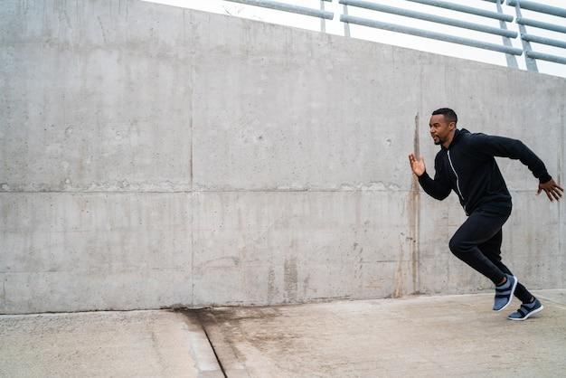 Ritratto di un uomo di fitness in esecuzione su strada contro il grigio.