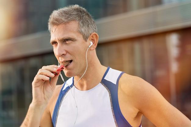 Ritratto di fitness uomo maturo mangiare una barretta energetica di cioccolato
