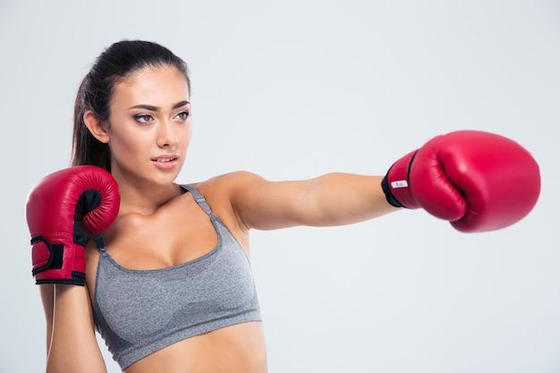 Ritratto di donna fitness boxe in guanti isolati su un muro bianco