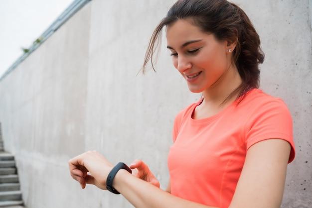 Ritratto di una donna di forma fisica che controlla il tempo sul suo orologio intelligente. sport e concetto di stile di vita sano.