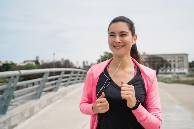 Ritratto di una donna fitness in esecuzione all'aperto in strada. sport e concetto di stile di vita sano.