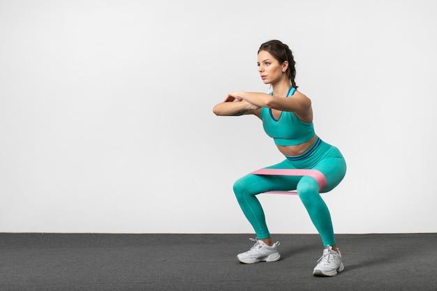 Ritratto di donna fitness in abiti sportivi con fascia elastica sulle gambe facendo esercizi di natica