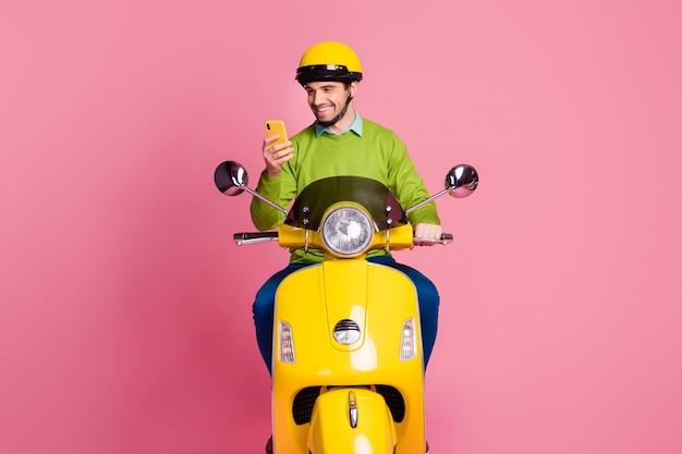 Ritratto di ragazzo concentrato in sella a una moto utilizzando il cellulare