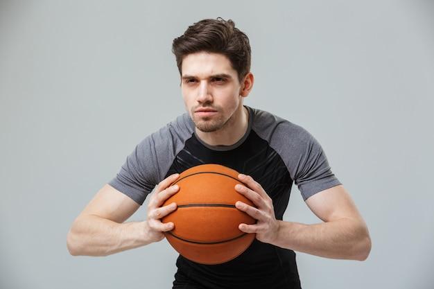 Ritratto di un giovane sportivo concentrato che gioca a basket