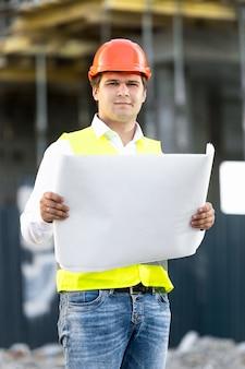 Ritratto di caposquadra in elmetto protettivo che legge i progetti sul cantiere