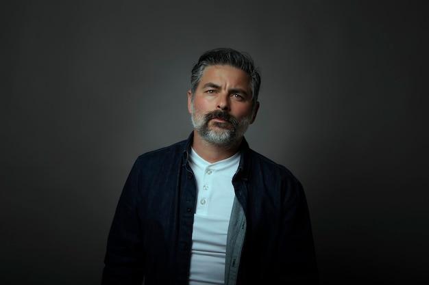Ritratto di un uomo caucasico di quaranta anni che indossa una sovrapposizione di camicia di jeans. muro nero, concetto scuro.