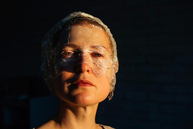 Ritratto di donna di quarant'anni con pellicola trasparente sul viso su sfondo nero con spazio di copia