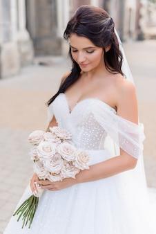 Ritratto di fragile sposa bruna in un vestito elegante con un mazzo di rose nelle sue mani