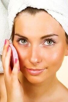 Ritratto di fresca e bella donna bruna che indossa un asciugamano bianco sulla sua testa