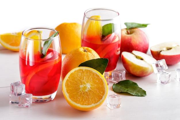 Ritratto di sciroppo fresco mix con arancia, fetta di mela e cubetto di ghiaccio