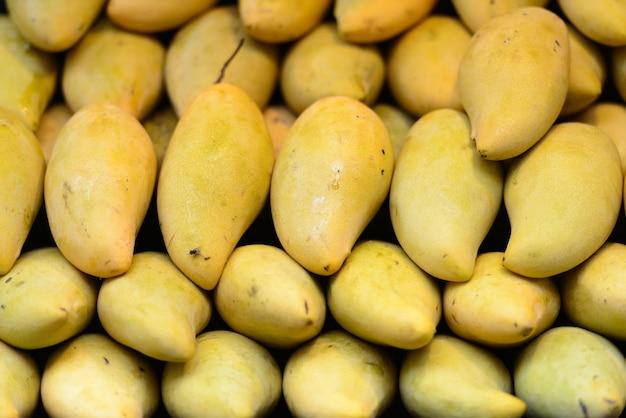Ritratto di manghi gialli maturi freschi ammucchiati nel mercato in vendita