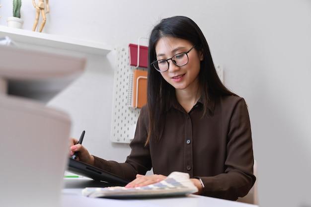 Ritratto di amichevole designer femminile sorridente e lavorando con forniture di design in ufficio