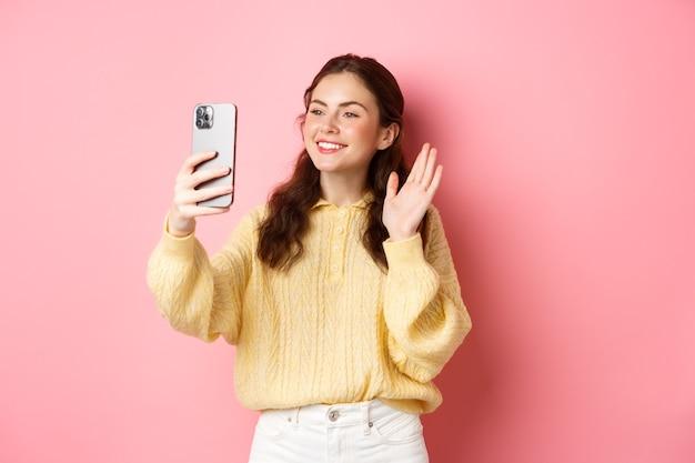 Ritratto di ragazza amichevole parlando su app di chat video, agitando la mano alla fotocamera dello smartphone, avendo una conversazione mobile, in piedi contro il muro rosa.