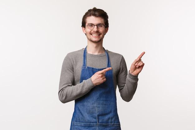 Ritratto di amichevole barista sorridente, imprenditore maschio inizia la propria piccola impresa, caffetteria che punta nell'angolo in alto a destra, invita a provare i suoi migliori drink in città, in piedi su un muro bianco