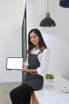 Ritratto di cameriera amichevole che tiene e mostra tablet digitale con schermo vuoto.