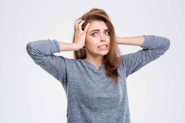 Ritratto di una donna spaventata che guarda l'obbiettivo isolato su uno sfondo bianco