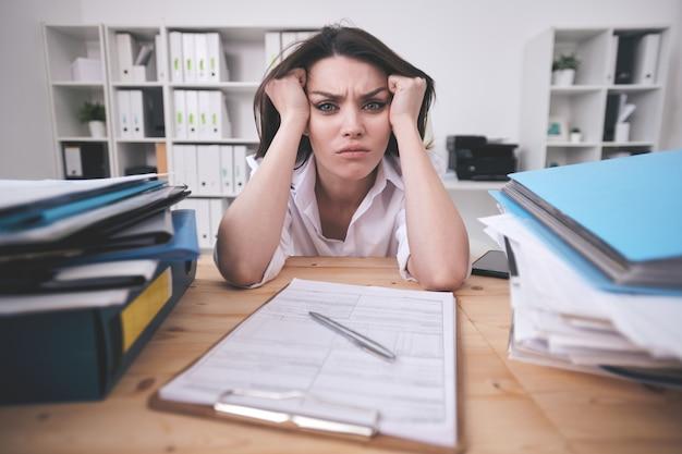 Ritratto di accigliata giovane imprenditrice confuso con scartoffie seduto con la testa tra le mani al tavolo dell'ufficio
