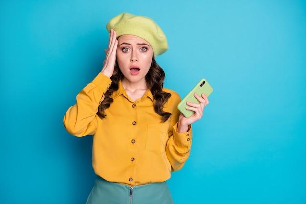 Il ritratto della ragazza frustrata usa lo smartphone legge le informazioni sul virus della corona dei social media impressionate toccano il copricapo delle mani isolato su uno sfondo di colore blu